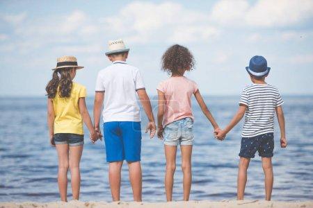 children standing at seaside