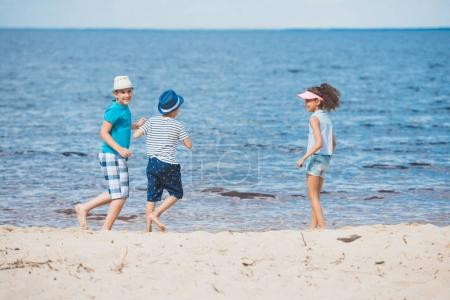 Multicultural children playing on beach