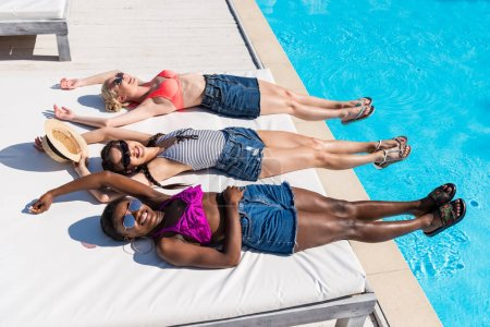 multiethnic women near pool at resort