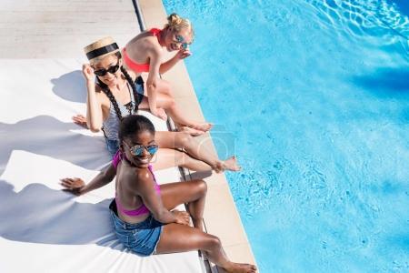 multiethnic women near pool at resort
