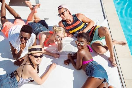 Photo for Group of young multiethnic friends rest at poolside during vacation at resort - Royalty Free Image