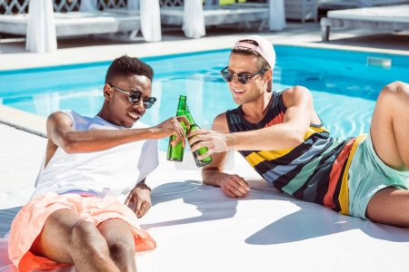 Multiethnic men with beer near pool