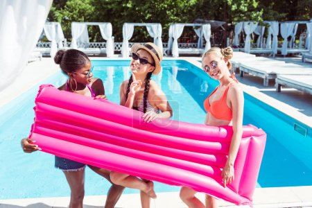 Multiethnic women with inflatable mattress near pool