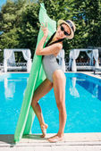 Asian woman with inflatable mattress near pool