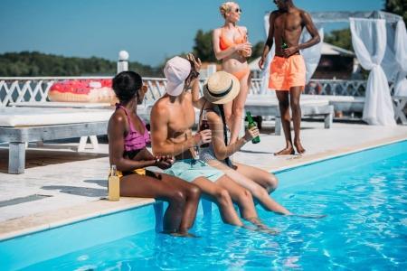 Foto de Grupo de jóvenes amigos multiétnicos sentado con bebidas en la piscina durante vacaciones en resort - Imagen libre de derechos