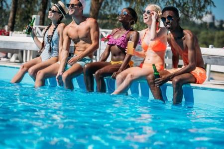 Photo pour Groupe de jeunes amis multiethniques assis avec des boissons au bord de la piscine pendant les vacances au resort - image libre de droit