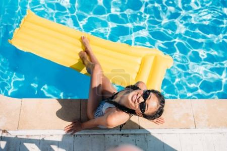 Photo for Top view asian woman resting near swimming pool at resort - Royalty Free Image