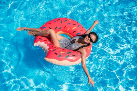 Photo for Young asian woman floating on inflatable donut in swimming pool - Royalty Free Image