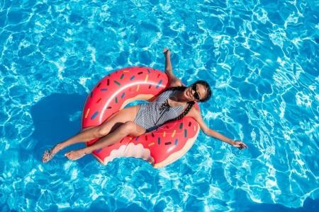 Photo pour Jeune femme asiatique flottant sur donut gonflable dans la piscine - image libre de droit
