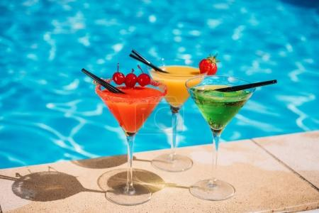 Photo for Colorful tropical cocktail with berries on edge of swimming pool - Royalty Free Image