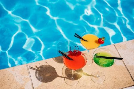 Photo pour Cocktail tropical coloré aux baies sur le bord de la piscine - image libre de droit