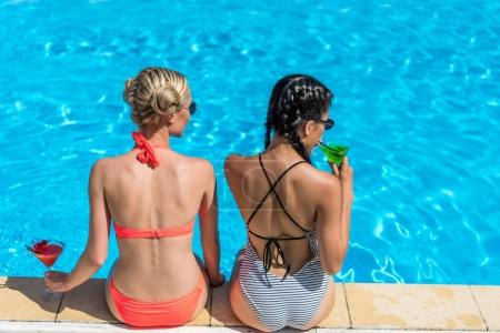 Photo for Young beautiful multiethnic women with cocktails sitting near swimming pool at resort - Royalty Free Image