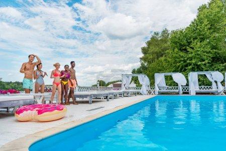 Multiethnic people on vacation near pool