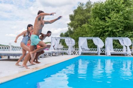 Photo for Group of beautiful young multiethnic people looking happy while jumping into the swimming pool together - Royalty Free Image