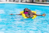 Woman on inflatable mattress in pool