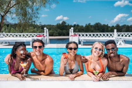 Photo pour Groupe de jeunes gens heureux multiethniques avec cocktails dans la piscine - image libre de droit