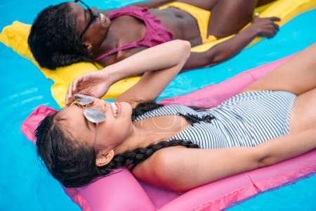 multiethnic women on inflatable mattresses in pool
