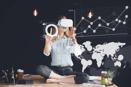 Photo for Businesswoman in virtual reality headset sitting in lotus pose on table in office and working with virtual diagrams - Royalty Free Image