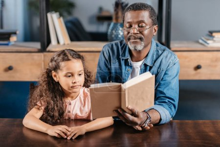 African american man reading with daughter