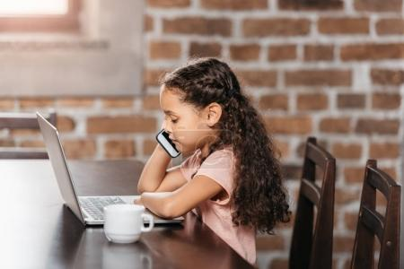 Photo for Cute african american girl using laptop and talking on phone at table - Royalty Free Image