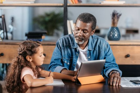 man using tablet with daughter