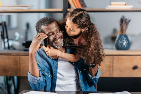 Photo for Cute african american girl hugging her father sitting at table and talking on phone - Royalty Free Image