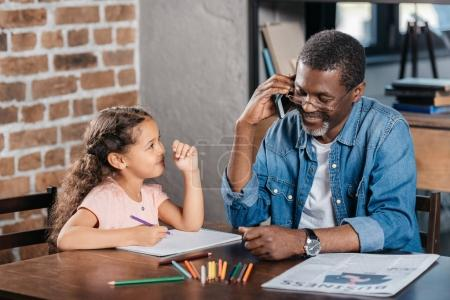 african american girl drawing with father