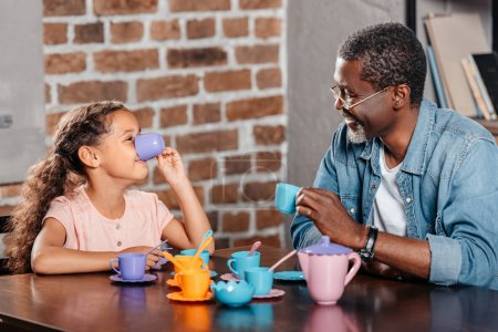 girl having tea party with father