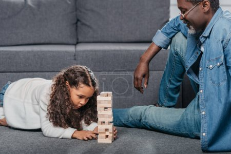 Girl playing blocks game with father