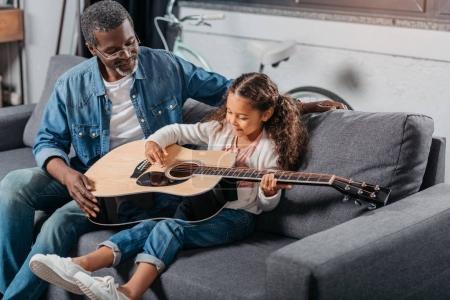 Man teaching daughter to play guitar