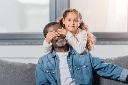 Photo for Adorable african american girl closing fathers eyes, standing behind him - Royalty Free Image