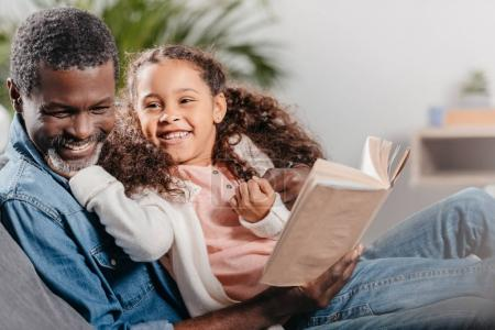 man reading book with daughter at home