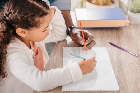 Photo for Cropped image of man helping his african american daughter drawing picture with colorful markers - Royalty Free Image