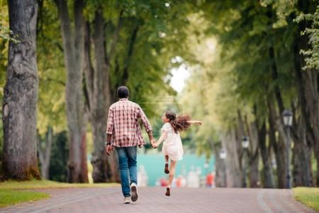 Photo for Back view of african american girl holding hands with grandfather, jumping and walking in park - Royalty Free Image