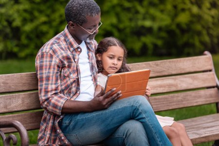 Photo for Adorable african american girl and her grandfather using digital tablet sitting on bench in park - Royalty Free Image