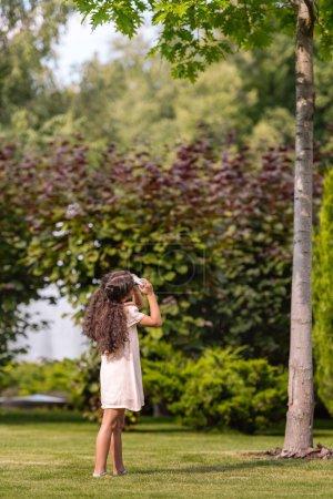 girl taking photo of tree