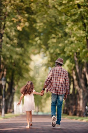 Photo for Back view of african american girl holding hands with grandfather and walking in green alley - Royalty Free Image