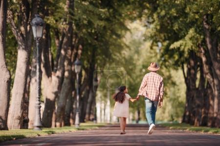 Girl with grandfather and walking in park