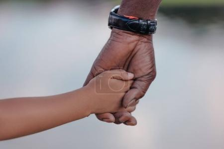 Photo for Cropped view of african american grandfather holding hands with granddaughter - Royalty Free Image