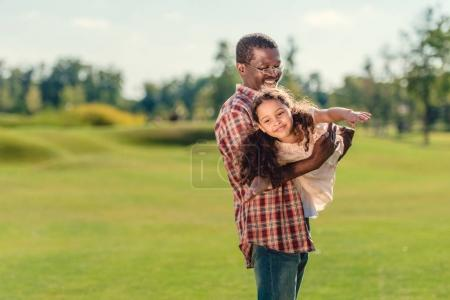 Photo for Smiling african american grandfather playing with happy granddaughter on green lawn at sunny day - Royalty Free Image