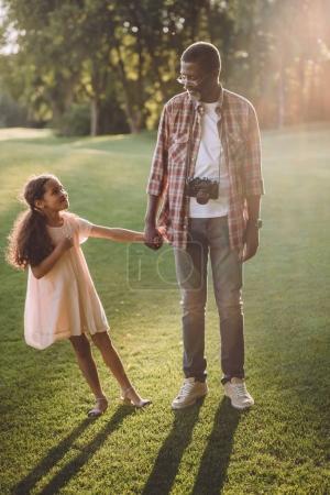 Photo pour Afro-américain avec appareil photo main dans la main avec sa petite-fille, debout sur la pelouse en plein soleil - image libre de droit