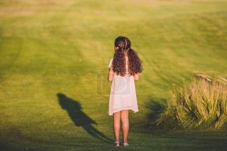 little girl standing on lawn