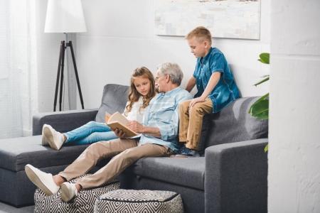 grandfather and grandchildren reading book