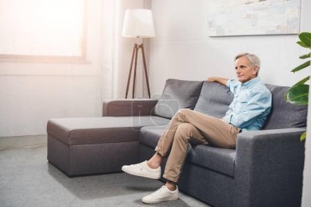 Photo pour Senior assis sur canapé à la maison avec contre-jour - image libre de droit