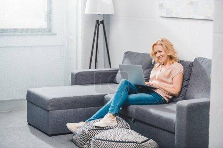 Foto de Mujer madura sonriente con laptop sentada en el sofá en casa - Imagen libre de derechos