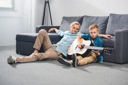 Photo for Grandfather and grandson playing on acoustic guitar while sitting on floor at home - Royalty Free Image