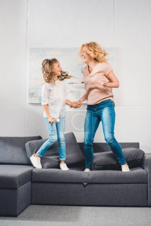 Granddaughter and grandmother jumping on sofa