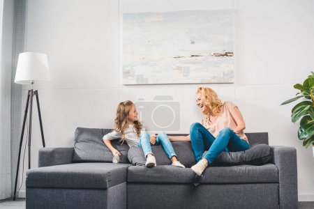 Photo for Happy granddaughter and grandmother having fun and sitting on sofa at home - Royalty Free Image