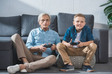 Photo for Grandfather and grandson playing video game with joysticks - Royalty Free Image
