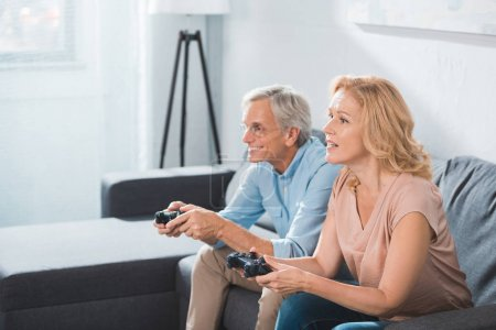 Photo for Focused husband and wife playing video game with joysticks at home - Royalty Free Image